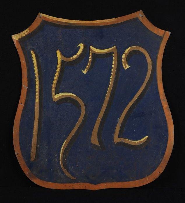 """Wapenschild met tegen tegen blauwe achtergrond opschrift in goud-geel """"1572"""""""