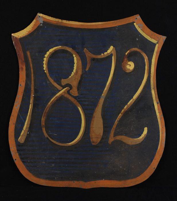 """Wapenschild met tegen blauwe achtergrond opschrift in goud-geel """"1872"""""""