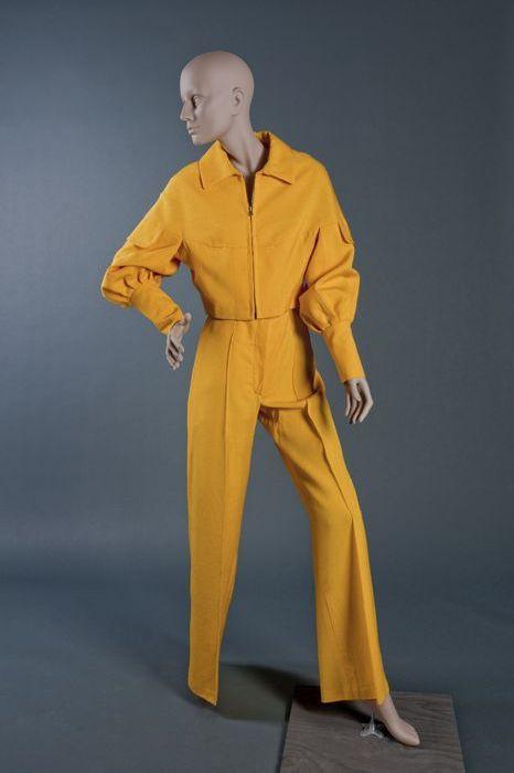 """Tweedelig broekpak van hardgeel linnen, getailleerde broek (2) met wijde pijpen, zeer korte jas (1) met lange manchetten en pofmouwen, klepjes op de schouders, """"Cargelli"""""""