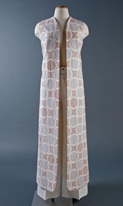 Voetlange, mouwloze gerende hes van piqué katoen met cirkelmotief in lila, wit en roze, rugsplit, voor twee cirkels bewerkt als zakken
