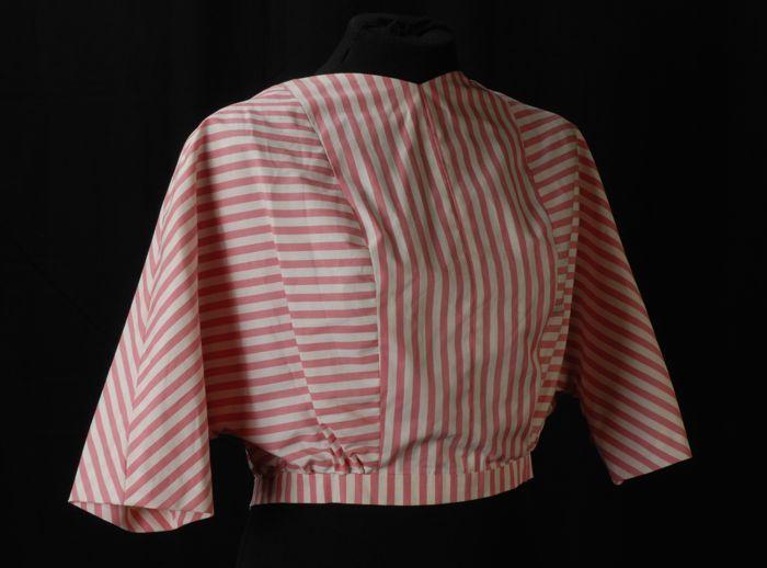"""Kort bloezend jasje van roze-wit gestreept katoen, driekwart vleermuismouwen en knoopsluiting op de rug, """"Cargelli"""""""