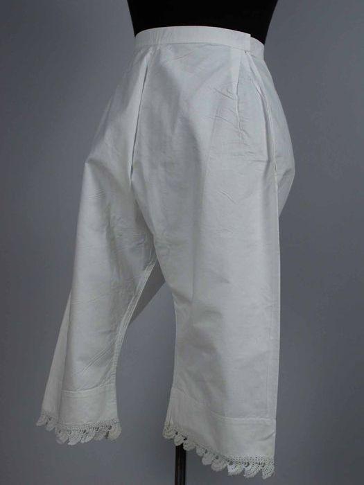 Onderbroek met pijpen van wit katoen, zijsplitten in de taille, gehaakte rand langs de pijpzomen