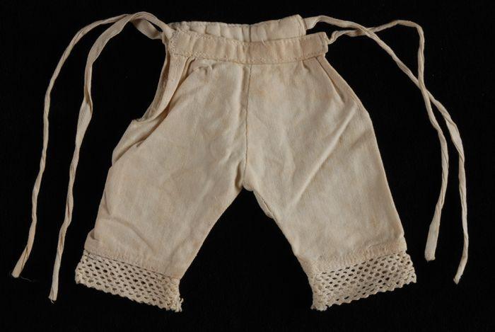 Lange poppenonderbroek van wit katoen met kant langs de pijpen, naaioefening