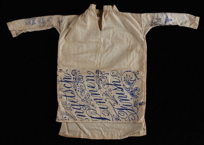 Poppenhemd van wit katoen met blauwe opdruk, naaioefening