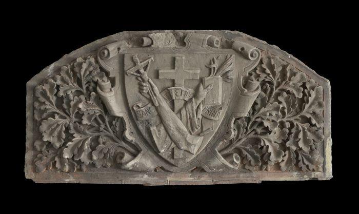 Gevelsteen met voorstelling kruis, kruisiging en boek: hartvormig schild omgeven door eikenbladeren en tekst